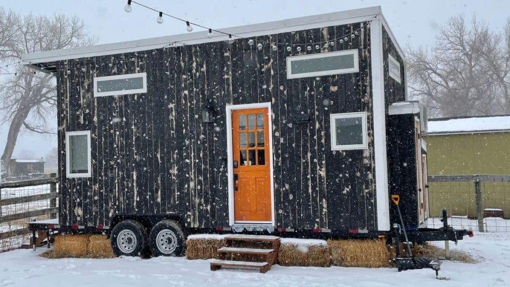Charcoal tiny home with orange door in snow