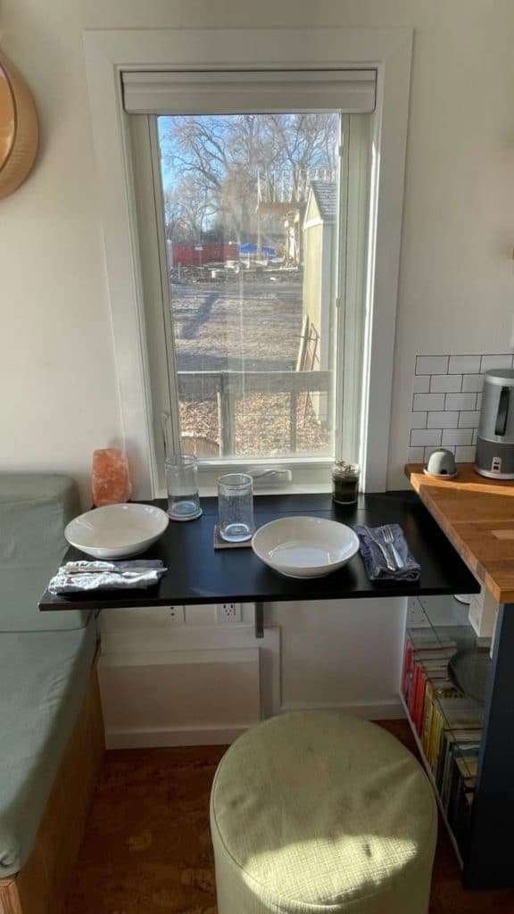 Black table by window with plates