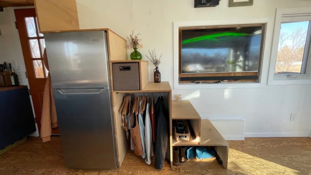 Stainless steel refrigerator with wooden stairs above it