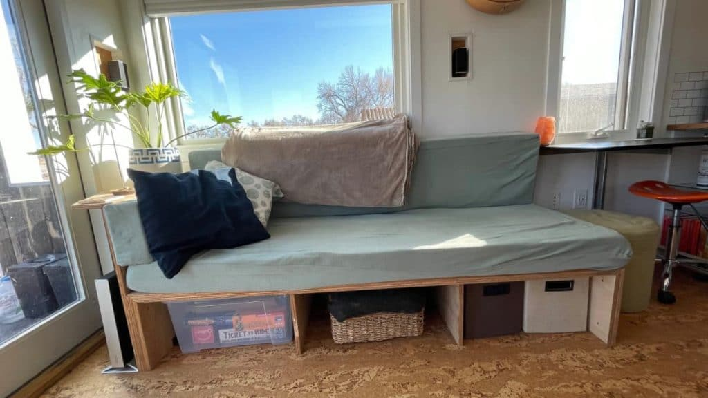 Light teal coach over open storage drawers