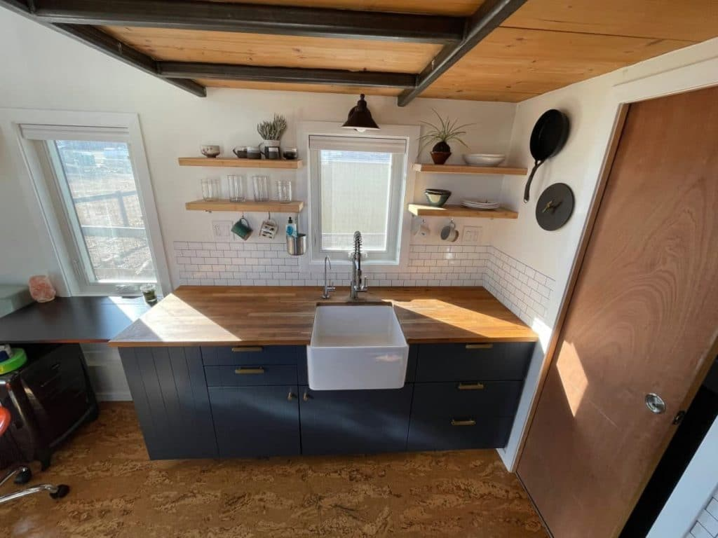 View of kitchen counter with floating shelves on wall above