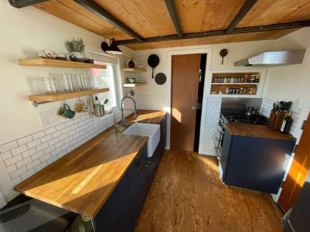 Butcher block counter on blue cabinets in farmhouse kitchen