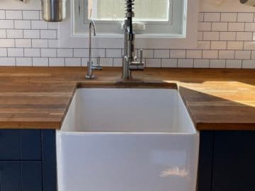 White sink in blue cabinet with butcher block counter