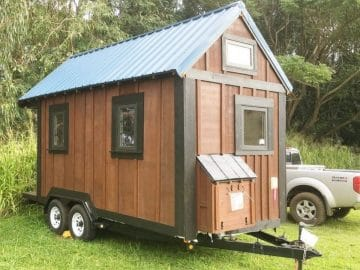 Tiny cedar cabin on grass by truck