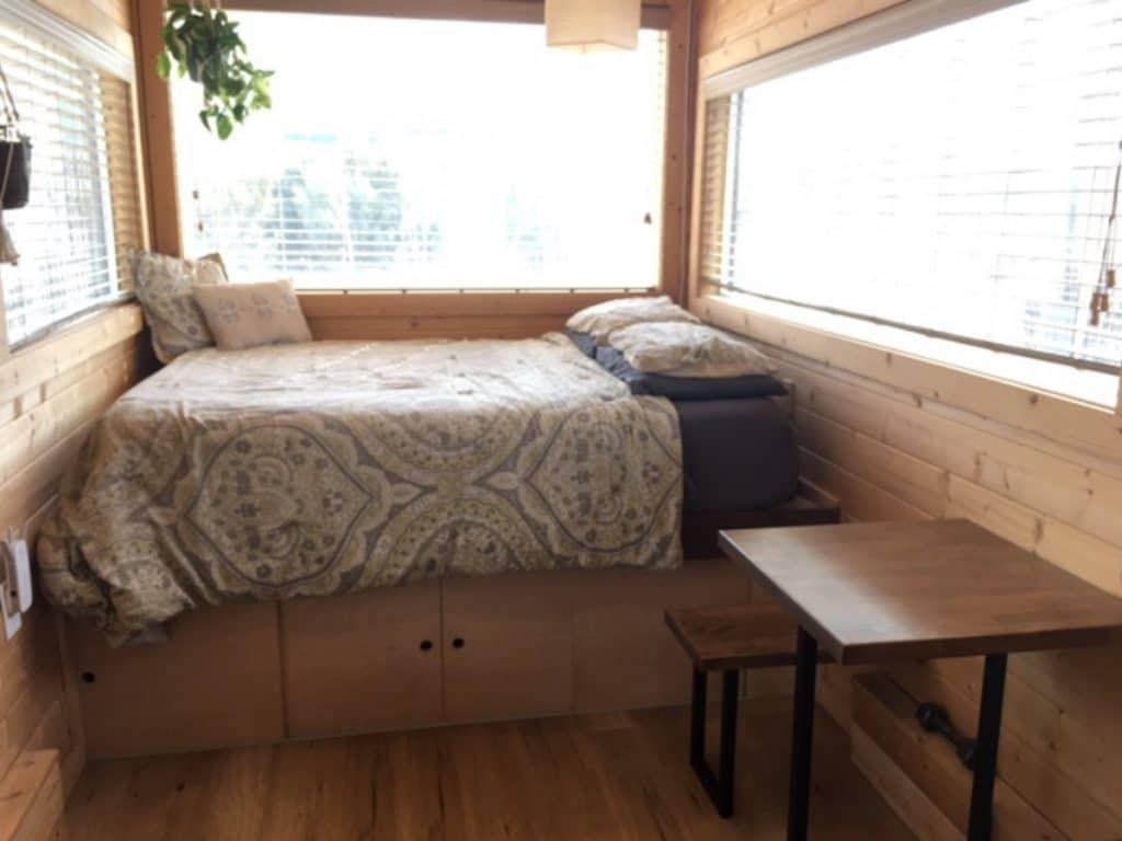 Bed on storage pedestal by windows
