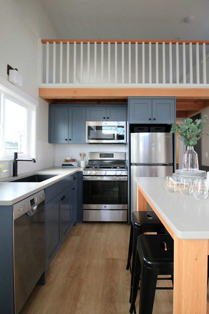 View into tiny house kitchen with island and stainless steel appliances