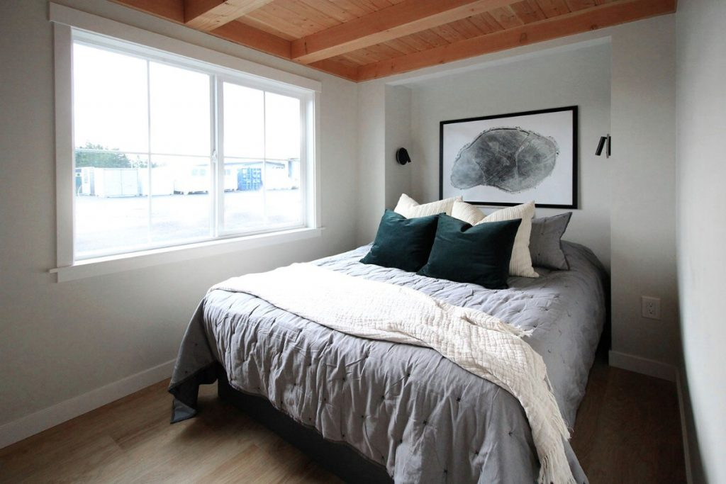 Small bedroom with bed by large windows