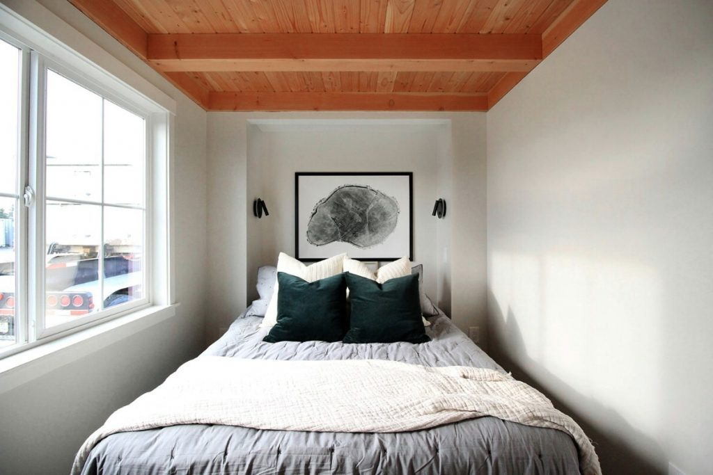 Small bedroom with bed by windows