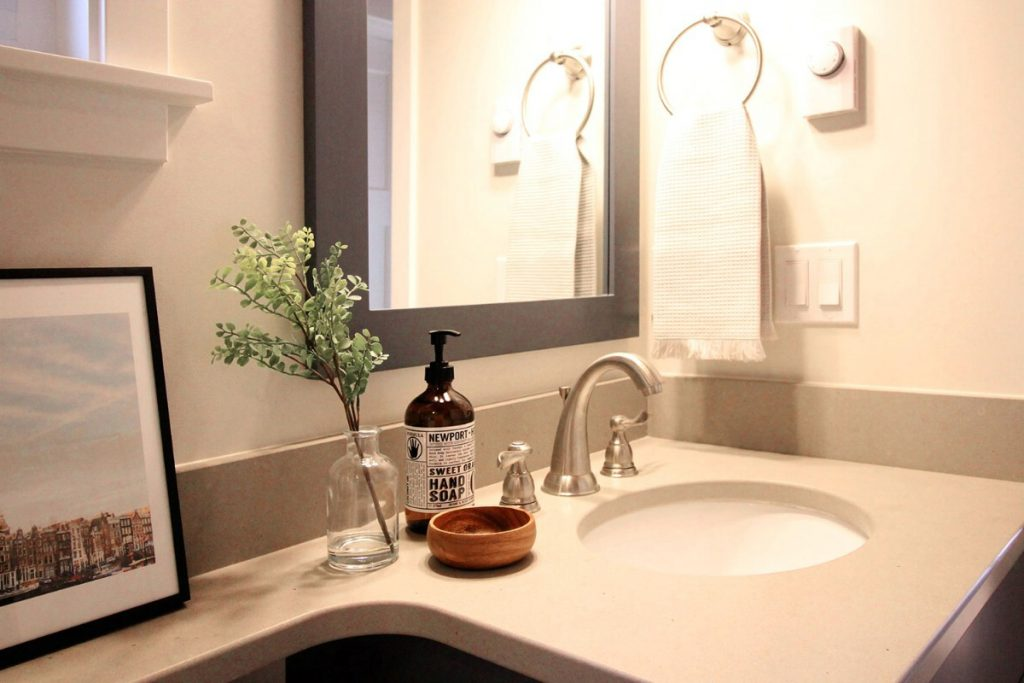 Bathroom sink with mounted mirror above