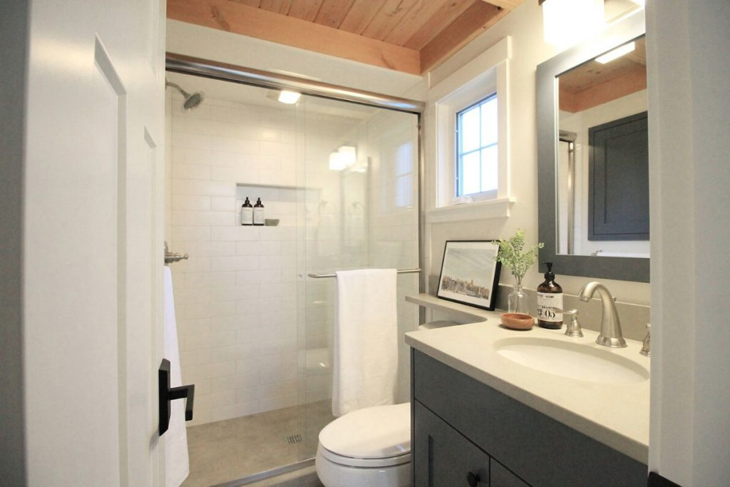 Bathroom with open glass shower and blue cabinet vanity