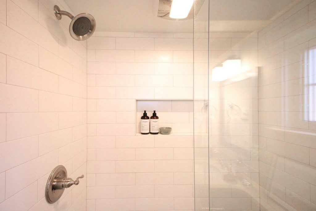 Shower stall with white tile wall