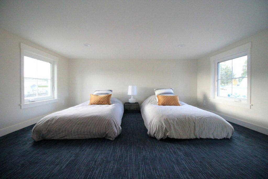 Twin beds in loft with bue carpet