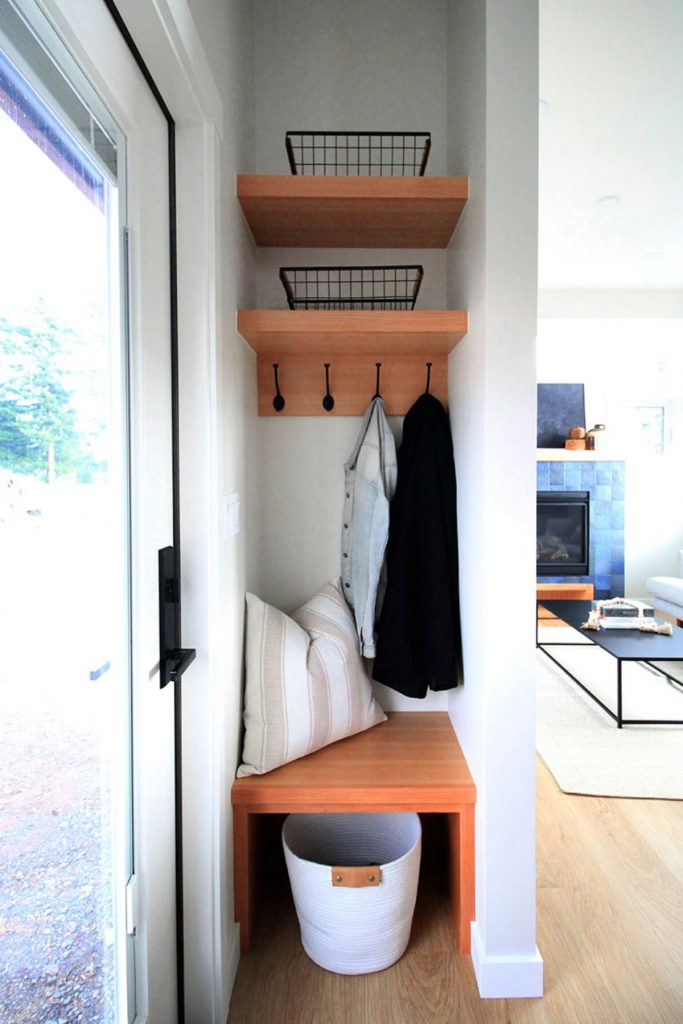 Closet inside the entry of tiny home with blonde wood shelves