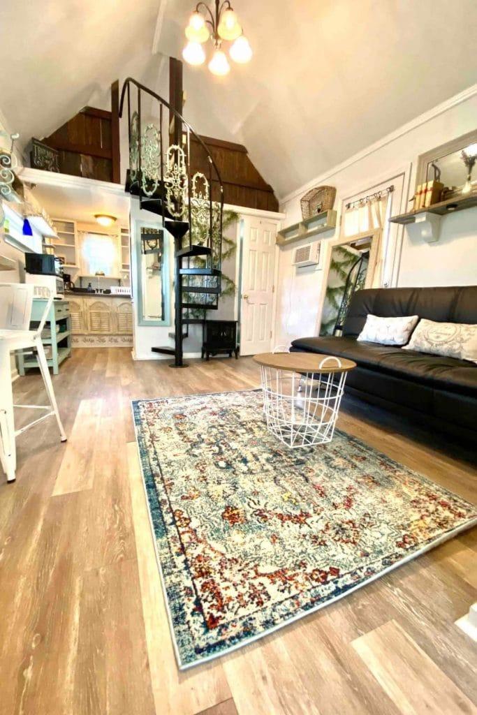 Colorful rug on blonde wood floor by dark sofa