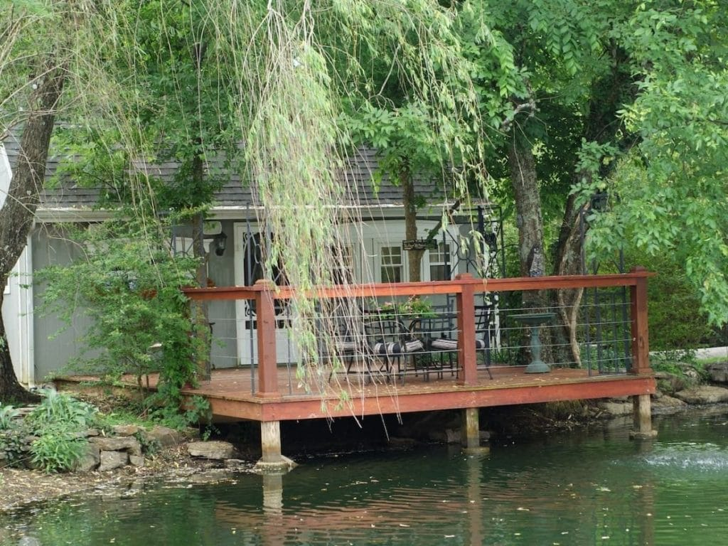 Tiny house hidden behind weeping willow tree