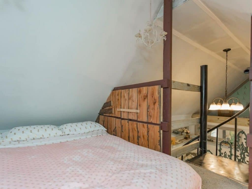 Edge of loft with stairs and bed under white ceiling