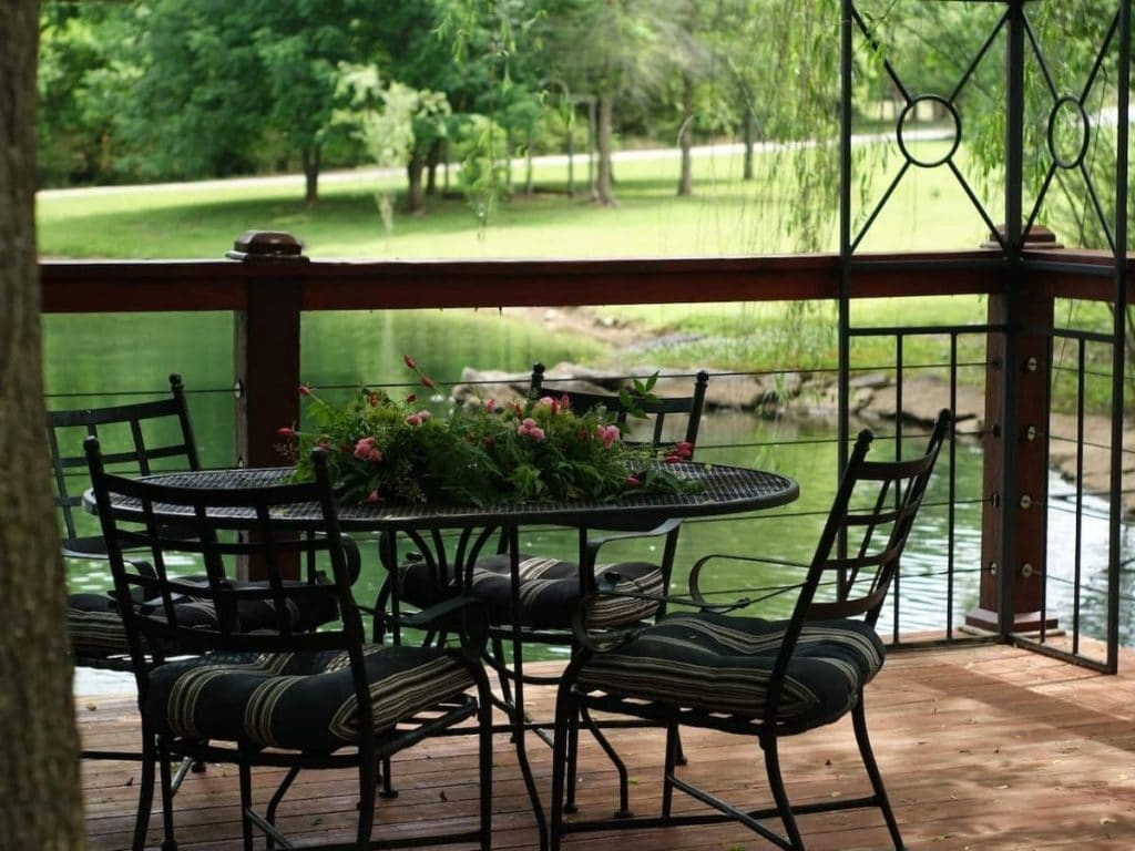 Patio by pond with black wire table and chairs