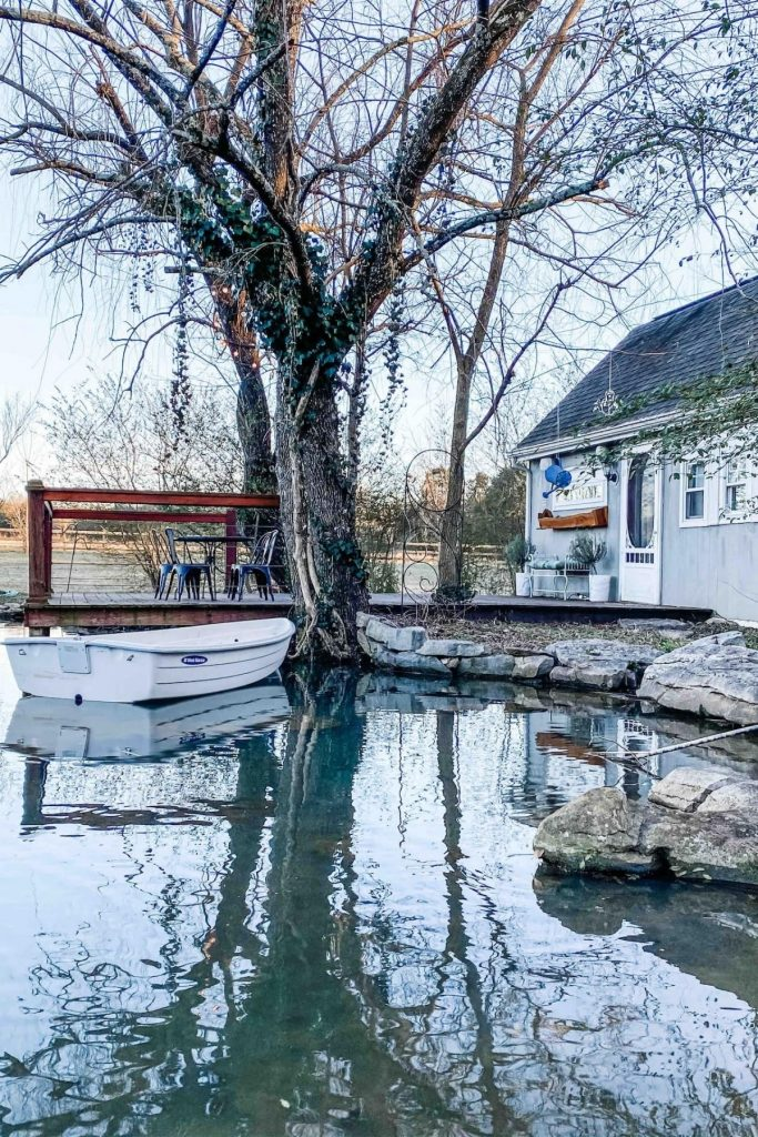 Grey tiny house by dock with white small boat