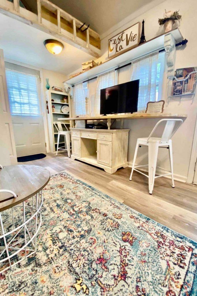 Colorful rug on floor below floating shelf holding television