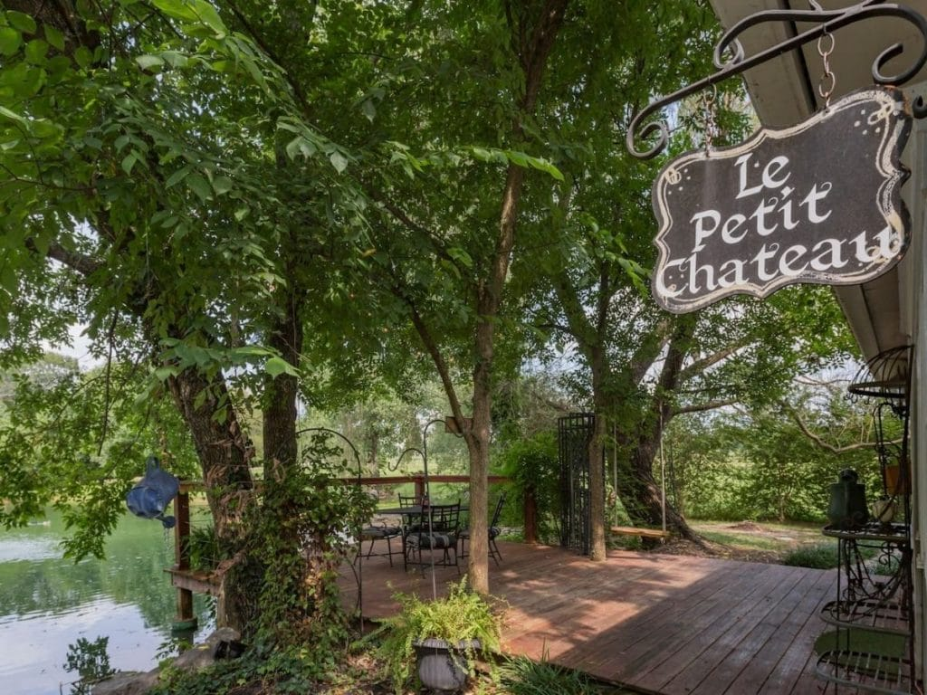 Sign hanging on home saying le petit chateau