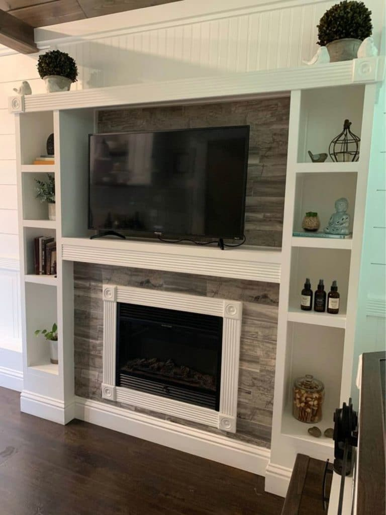 Fireplace surrounded by white shelving and entertainment center