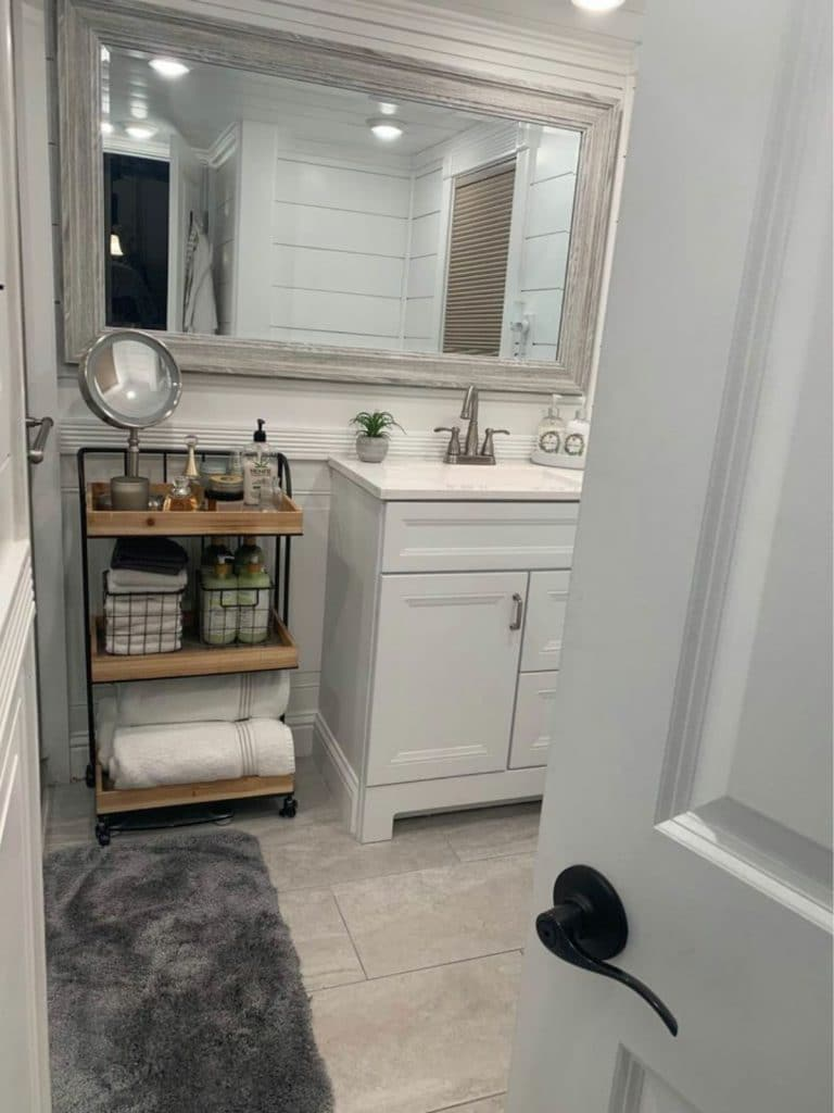 Vanity in bathroom with large mirror above