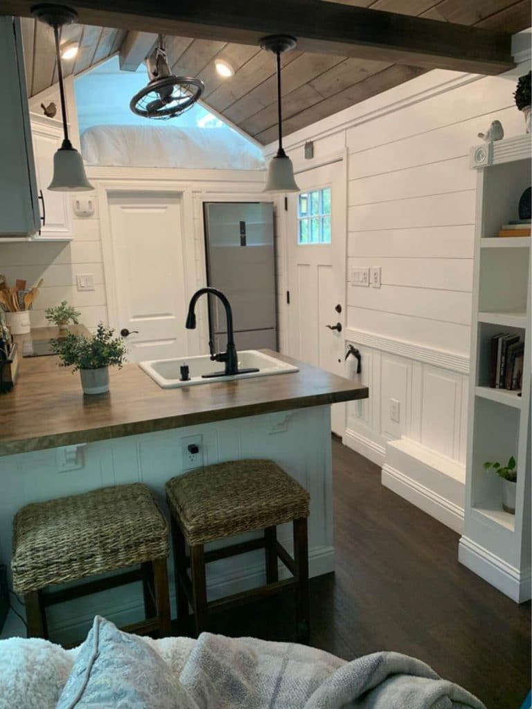 View into kitchen with white shiplap walls