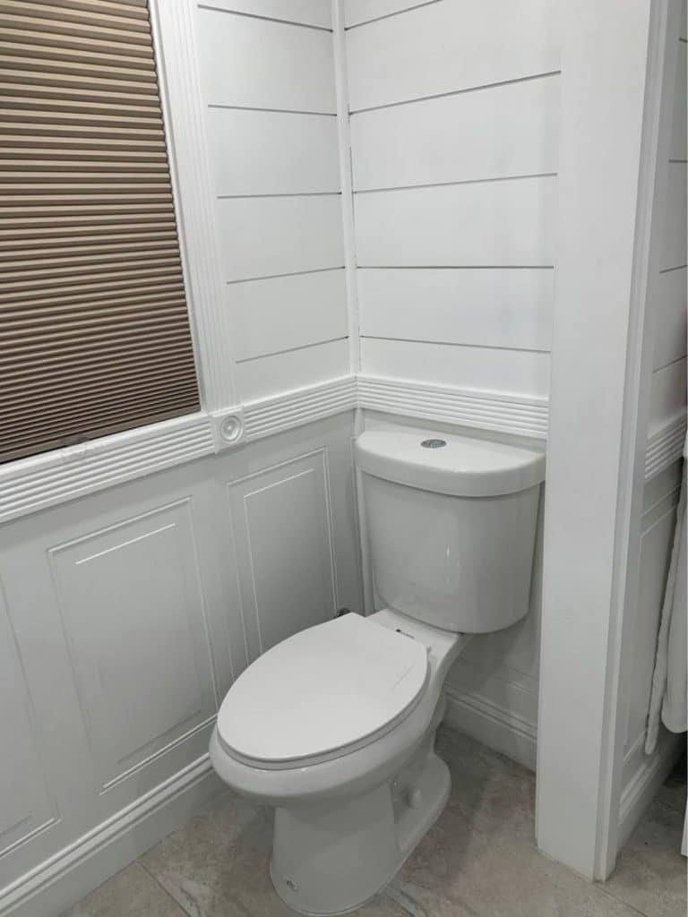 Toilet surrounded by white shiplap