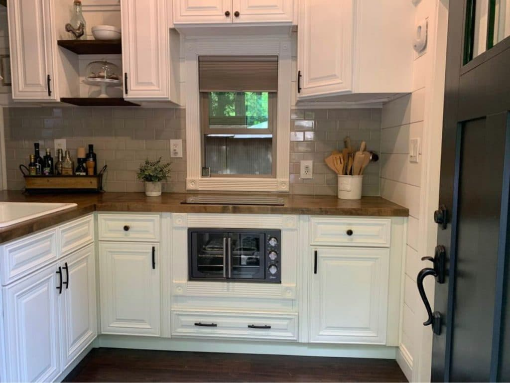 White cabinets with oven built in and butcher block counter