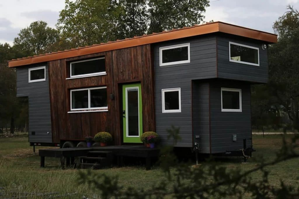 Grey and brown tiny home with green trim