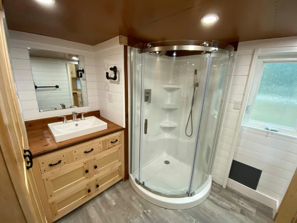 Round shower stall next to natural pine vanity with white sink