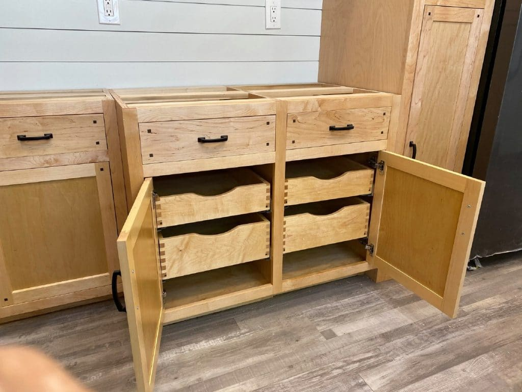 Open doors on cabinets showing wooden drawers inside
