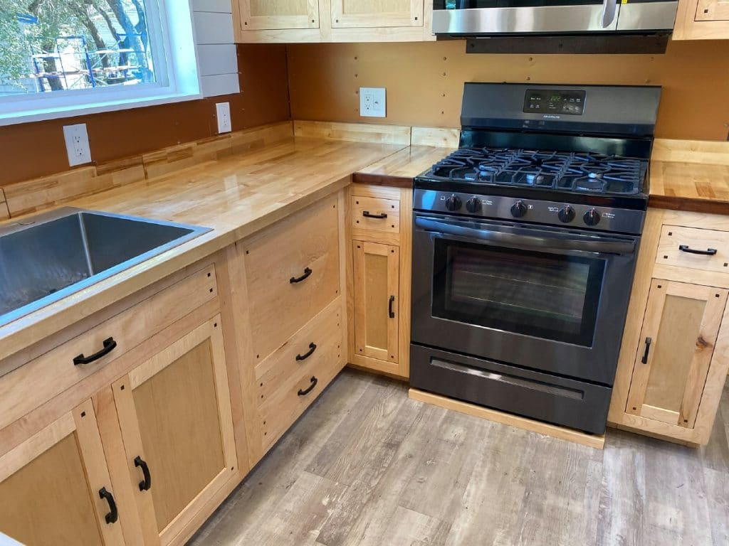 Black gas stove inset in pine cabinets
