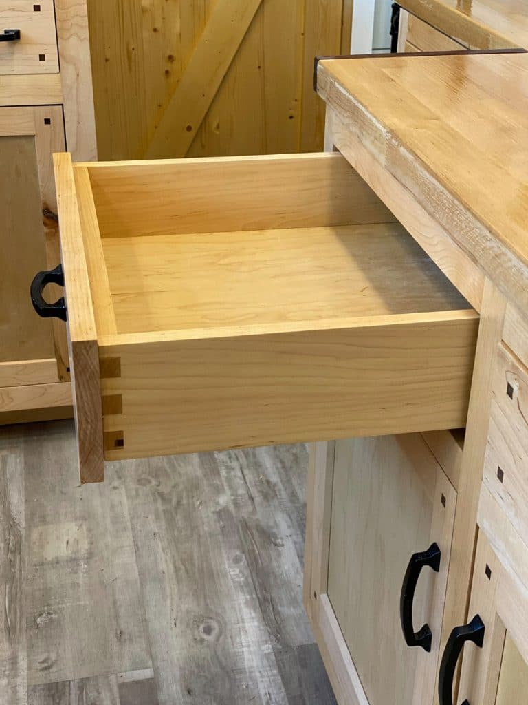 Drawer pulled out of natural pine cabinet