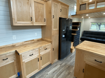 White shiplap wall kitchen with natural pine cabinets and black appliance