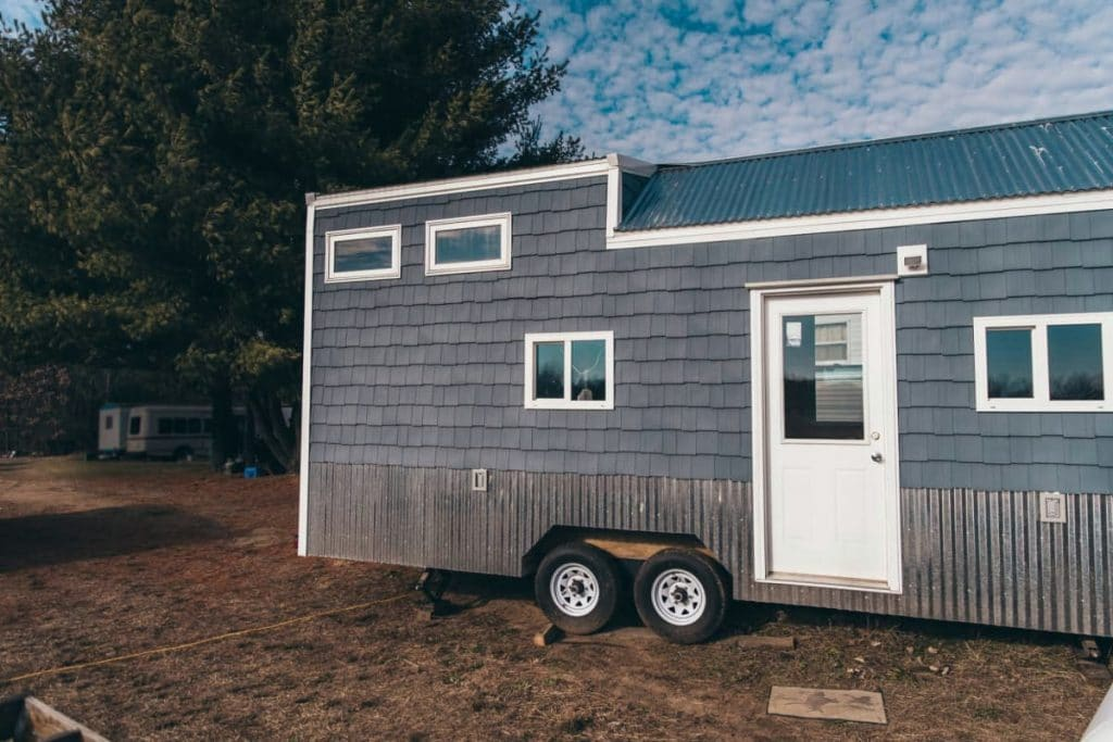 Blue tiny house with loft and white trim