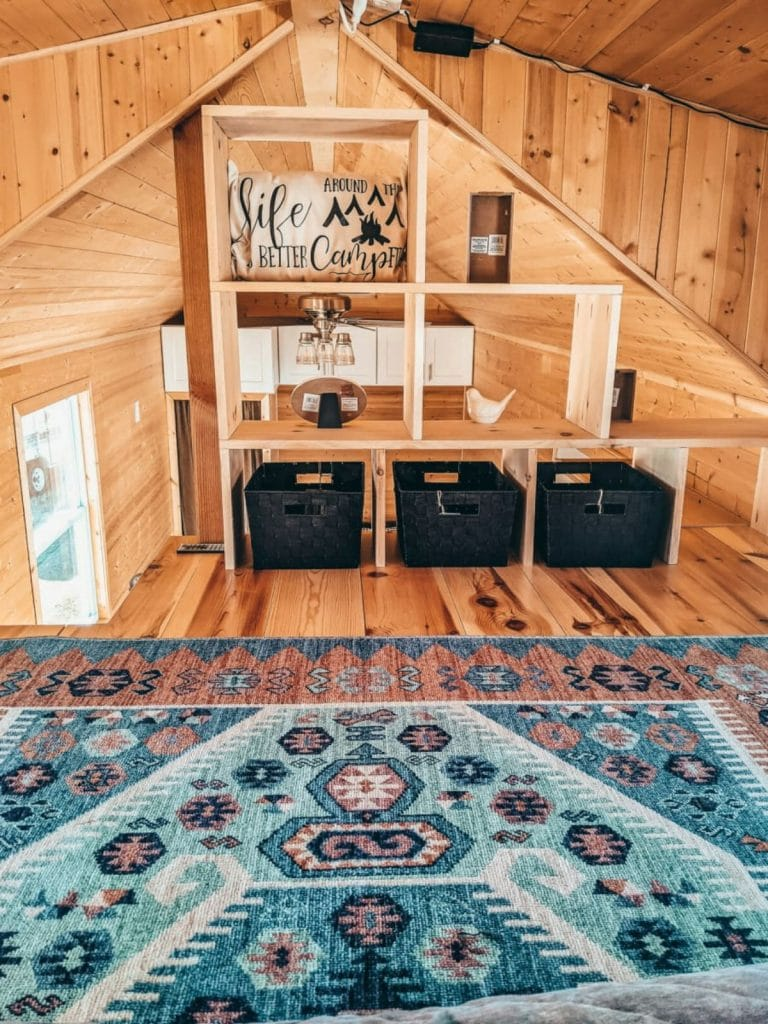 Colorful rug in tiny home loft with black bin storage