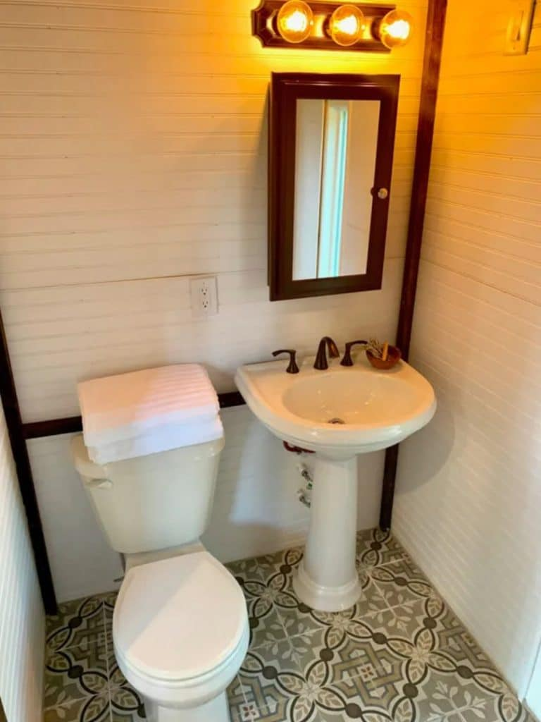 White bathroom with tile floor and pedastal sink