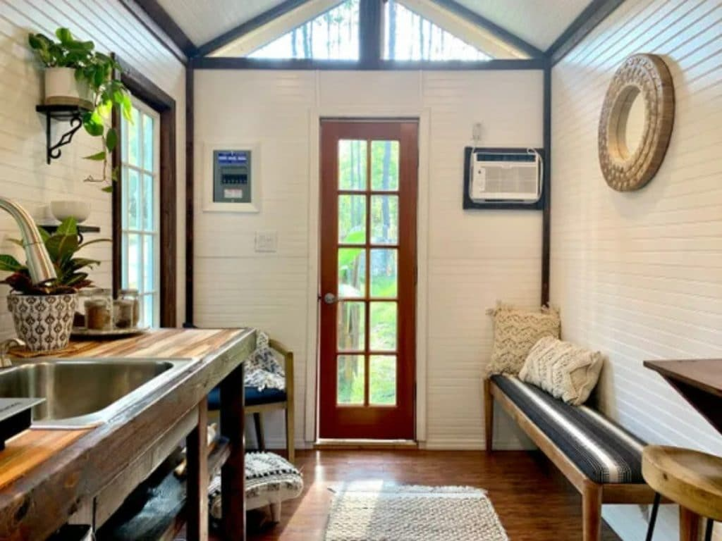 Inside living space of tiny home with orange glass paned door