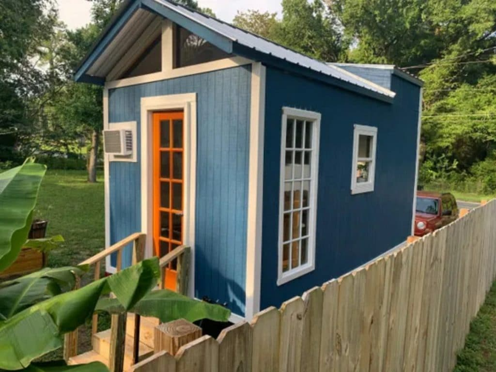 Tiny blue house with white trim and orange door