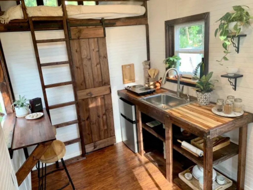 View of wood barn door to bathroom and ladder to loft