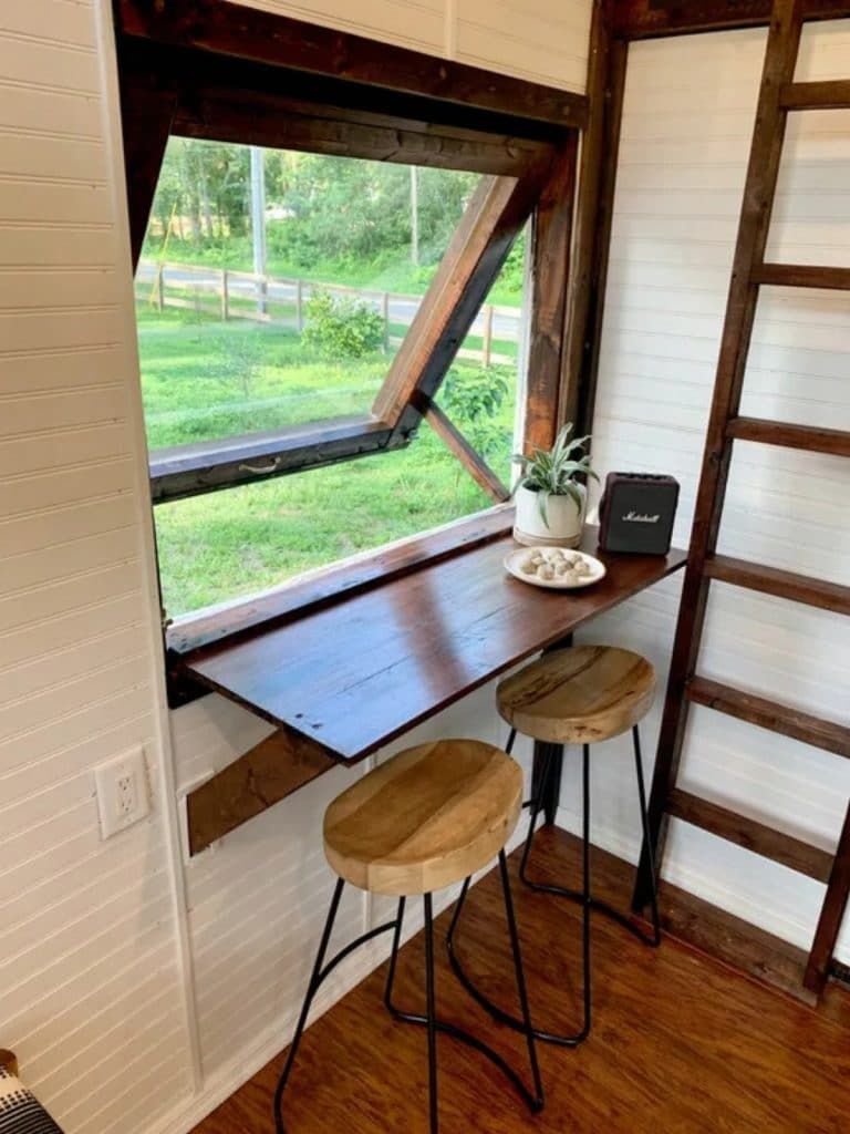 Window table with stools below and wood ladder in background