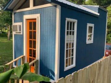 Blue tiny house with white trim and orange door