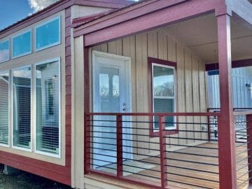 Tan and maroon tiny house with covered porch on lot