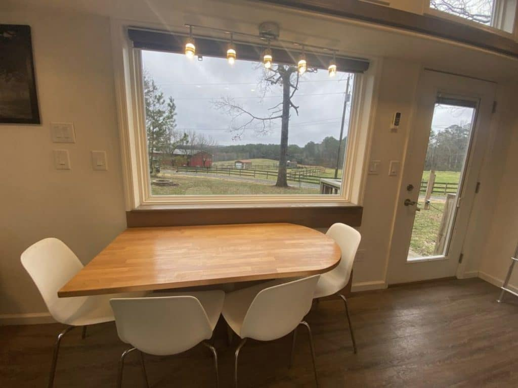 Wooden table with two chairs by large window