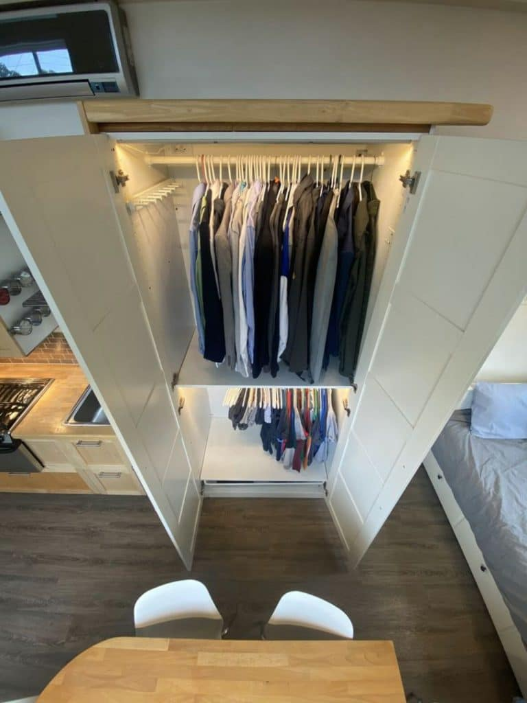 Open doors of tall white wardrobe with hanging cloths