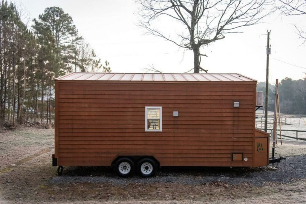Back of brown tiny home with middle window