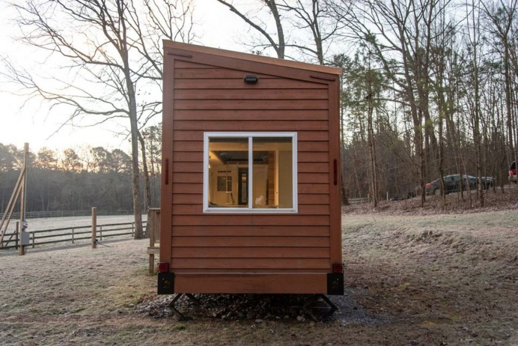 End of brown tiny home with two windows