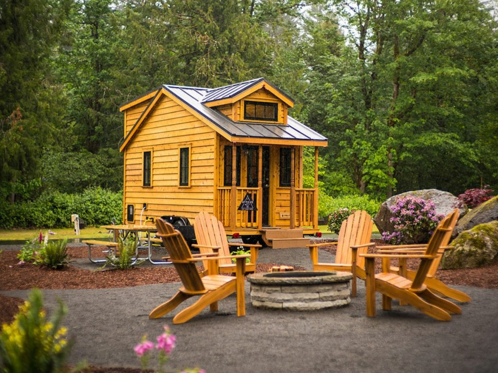 Tiny cabin with by tree with adirondack chairs around fire pit