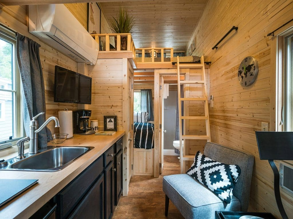 View from tiny home front door into loft with wooden ladder